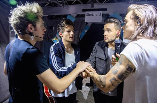 The boys of One Direction huddle for some final words of encouragement before they head on stage.