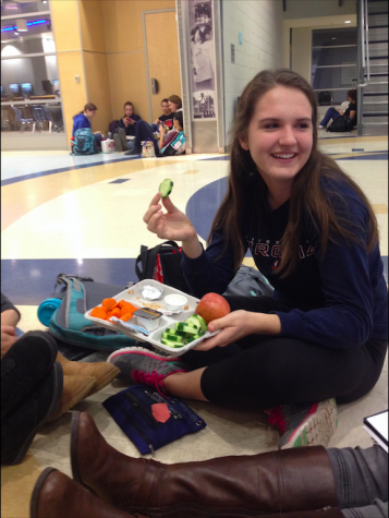 Sophomore Cara Ford enjoys her lunch of a chicken sandwich, cucumbers, an apple and milk while talking to her friends