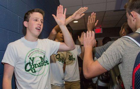 Senior Noah Kline welcomes incoming freshmen with a high five.