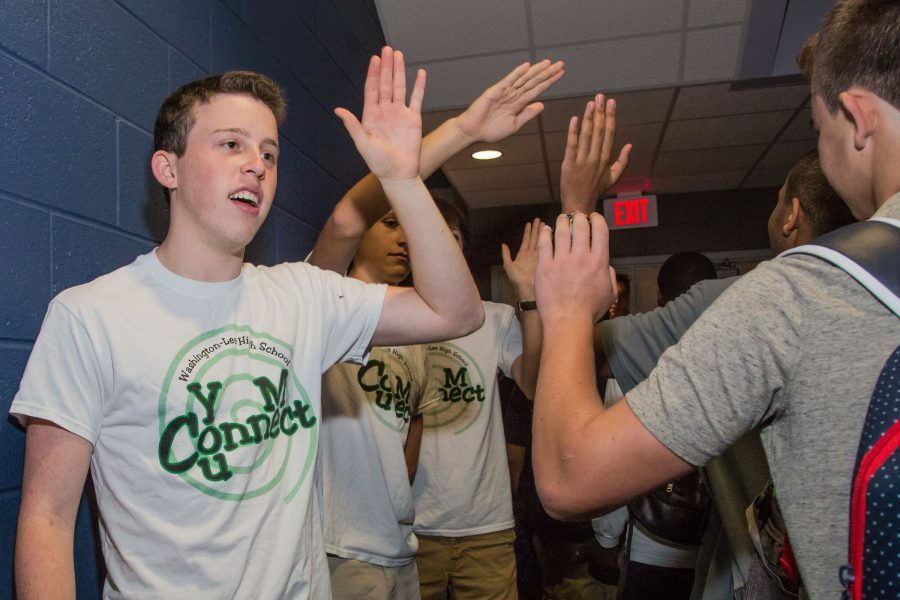 Senior Noah Kline welcomes incoming freshmen with a high five.
