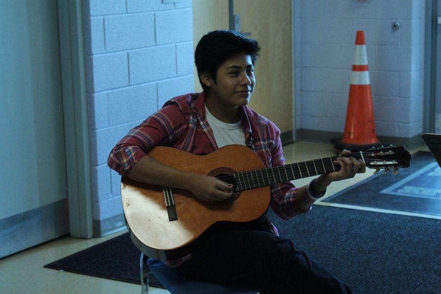 Senior Daniel L. practices guitar for his performance of