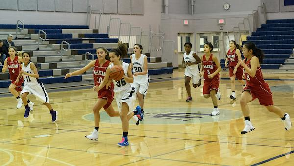 Sophomore Alexis Parks runs down the court as she attempts to guard the ball from a McLean player.