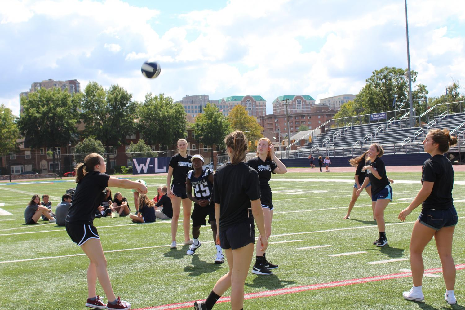 The varsity volleyball team gets the ball in the air to pump themselves for the pep rally