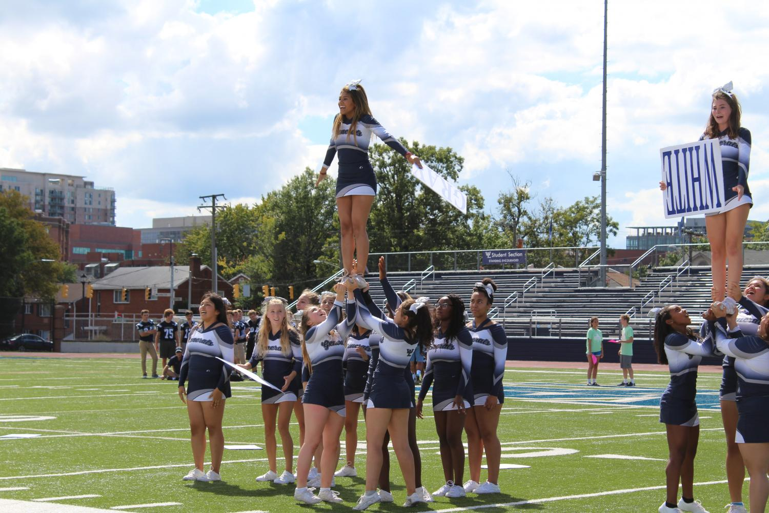 The varsity cheer team lift up one of their members during a special move in their routine