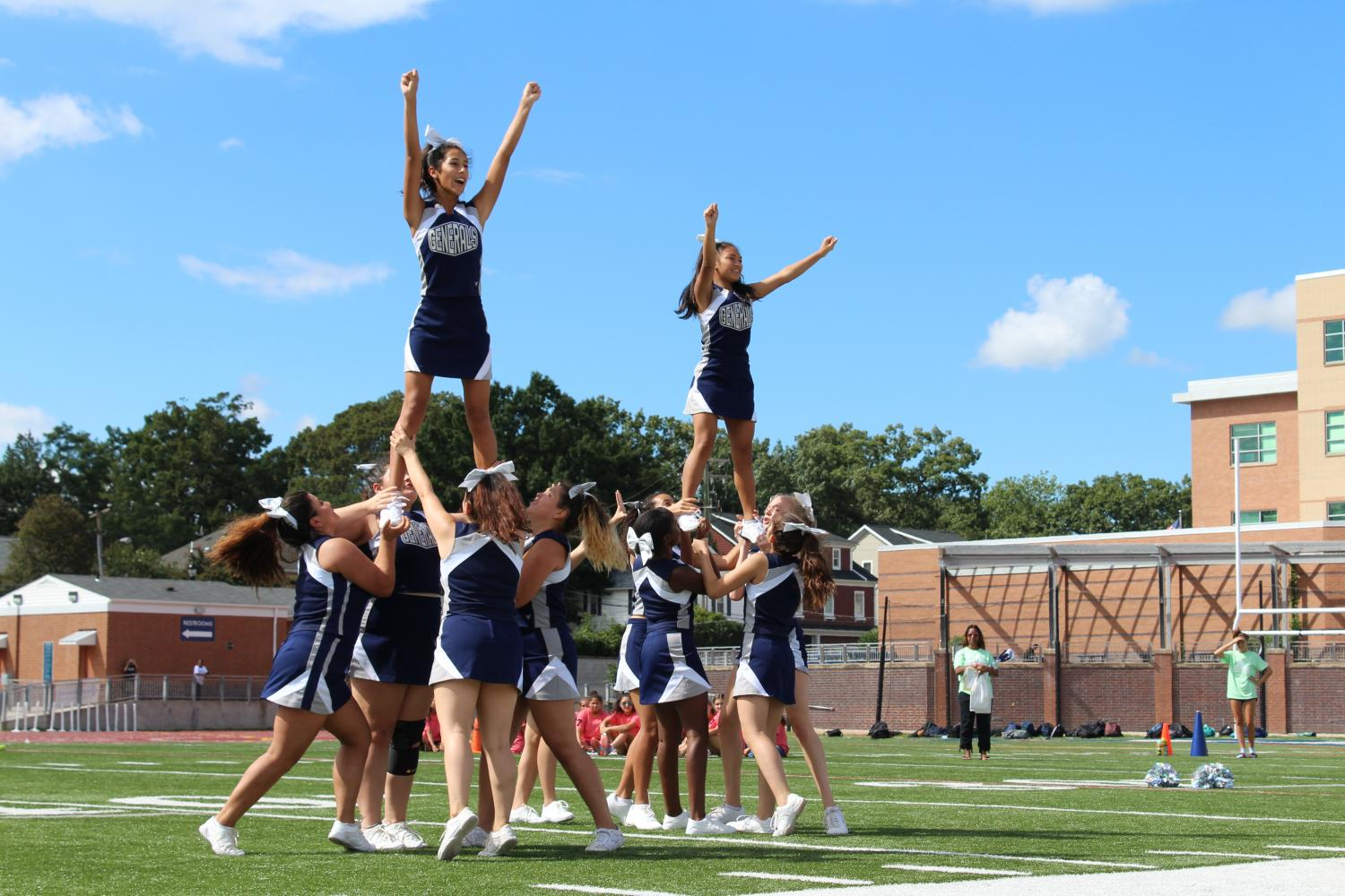 The JV cheer team lifts two of their members to pump up the crowd at the pep rally