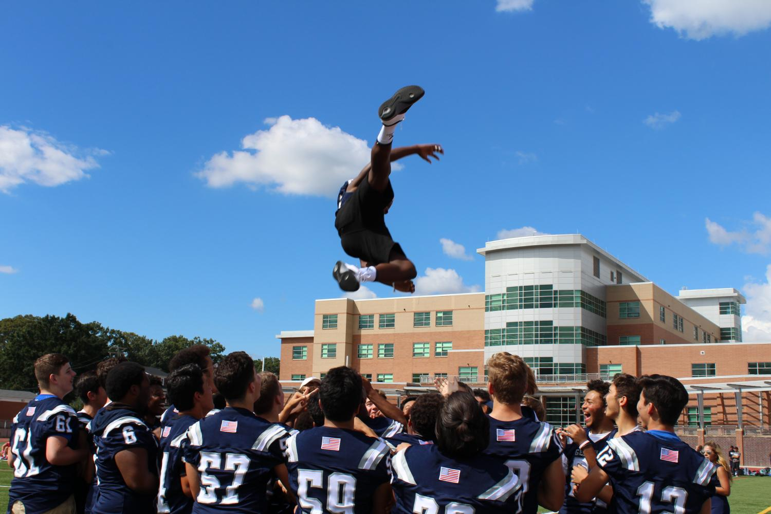 The varsity football team energizes the crowd by throwing a team member into the air