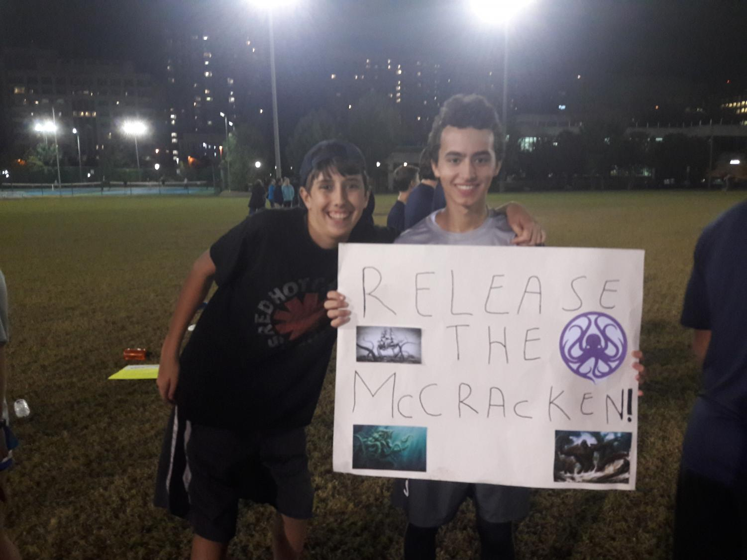 Sophomore Ethan Burka and junior Adam Edwards hold up a sign for the Frisbee team's Senior Night.