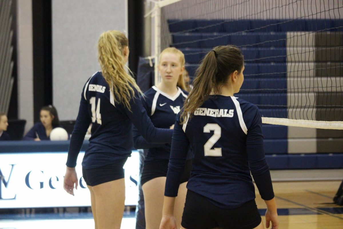 Varsity+volleyball+players+Genevieve+Bernard%2C+Kate+Sheire+and+Hannah+Demas+stand+at+the+net+in+between+plays.