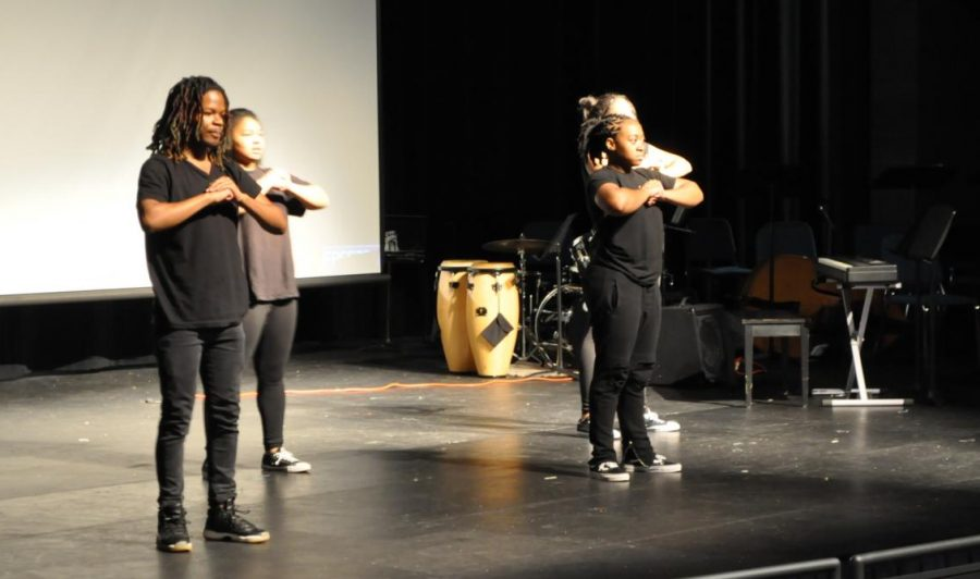 Savage performs a percussive dance on stage at the assembly.