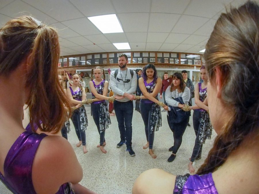 The Winter Guard team has a group huddle before a competition.
