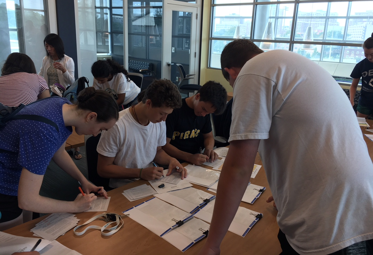 Juniors Julia Timpane and Angelo Lepore and senior Matthew Hopper sign postcards for the incoming freshmen. Every year the mentors mail out a card with a short letter about the Connect Mentors Program for each freshman.