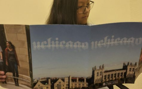 Sophomore Paige Dillon reads the University of Chicago's pamphlet. Visiting colleges often provide information in these pamphlets, such as financial aid programs and graduation rates.