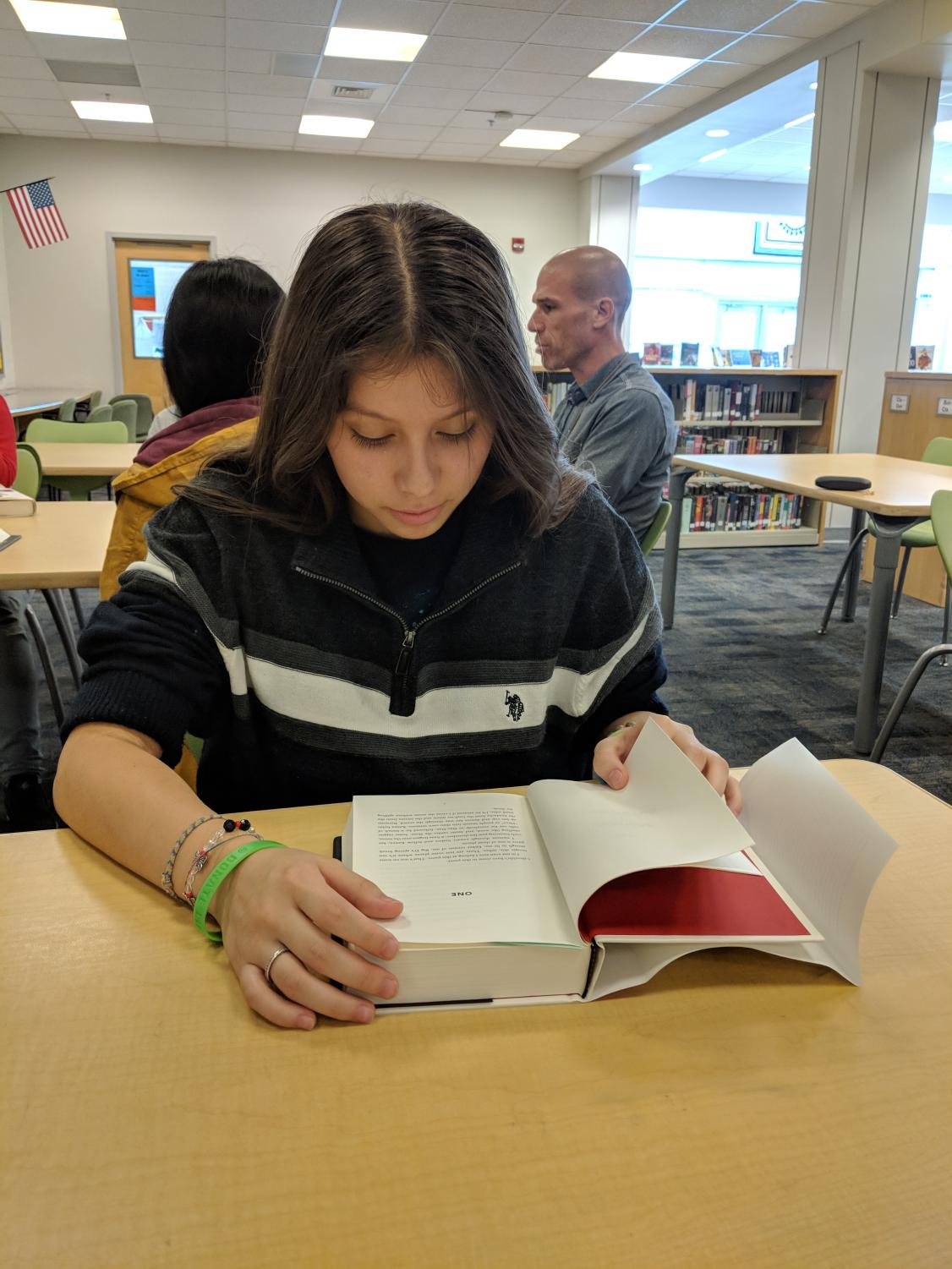"""Freshman Emely Interiand begins reading """"The Hate U Give"""". The book was made into a movie and released on October 5 of this year."""