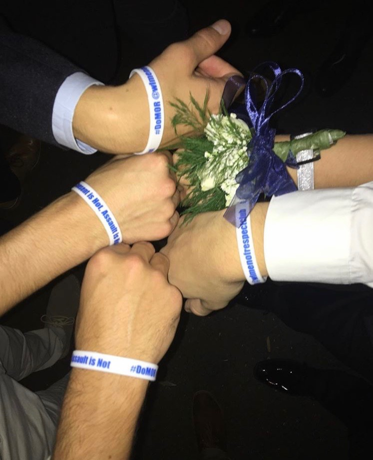 The Men of Respect club holding out their wristbands alongside homecoming goers