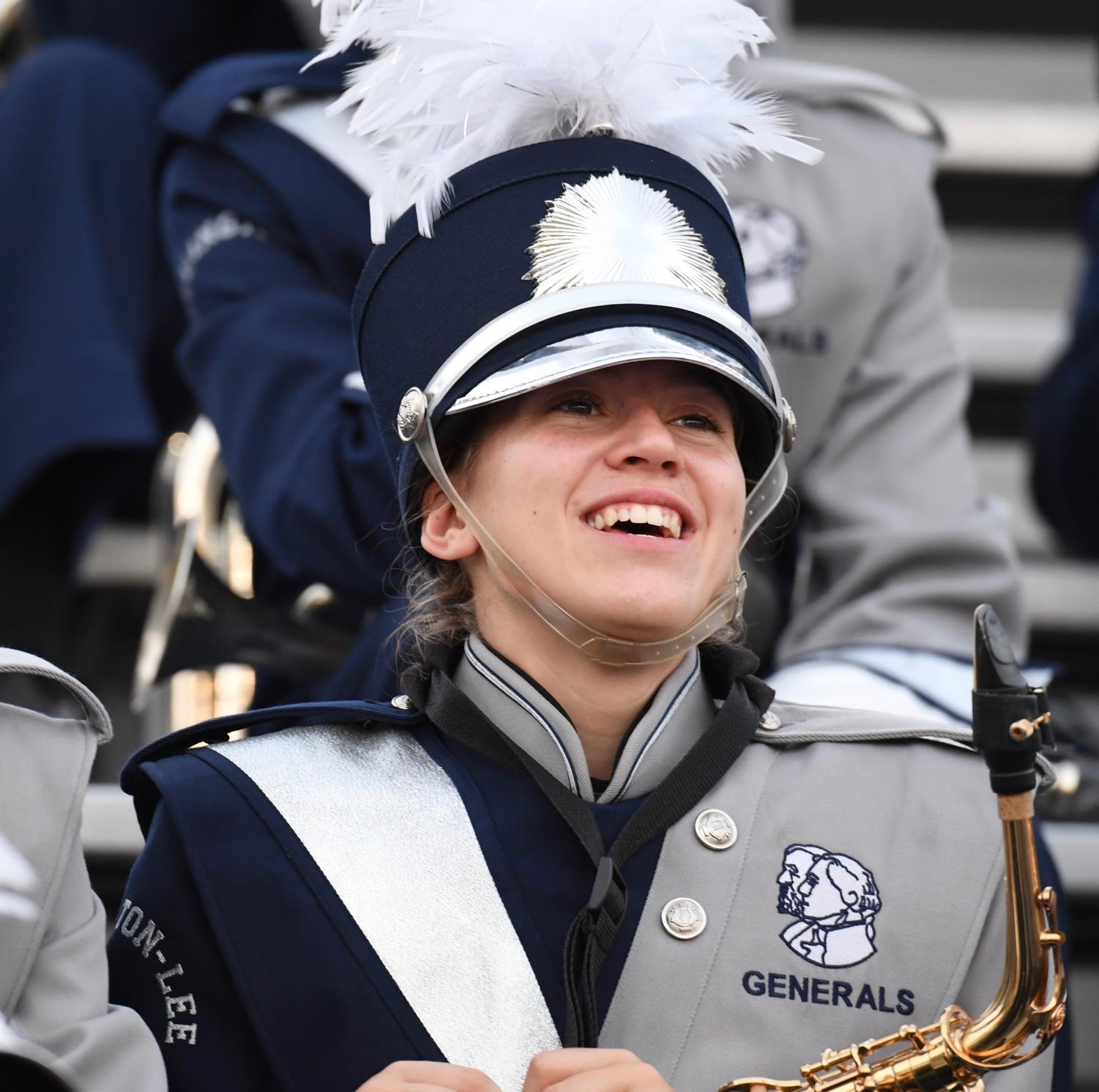 Senior CeCe Collinson smiles at the camera while sitting in the stands with the rest of the marching band.