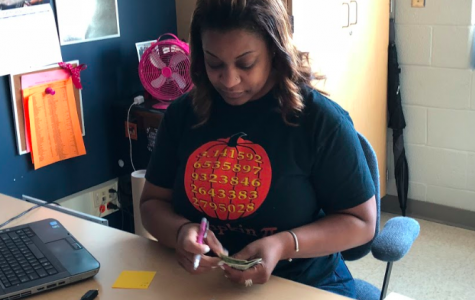 Student Council Association (SCA) advisor Ms. Timica Shivers counts money. The SCA is involved in school events throughout the year, such as the annual Homecoming dance.