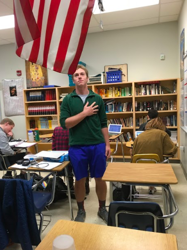Senior Owen Potts stands for Pledge of Allegiance at the beginning of their busy day. As staying seated for the pledge has become a popular form of protest, some have been offended by students' choices not to stand.