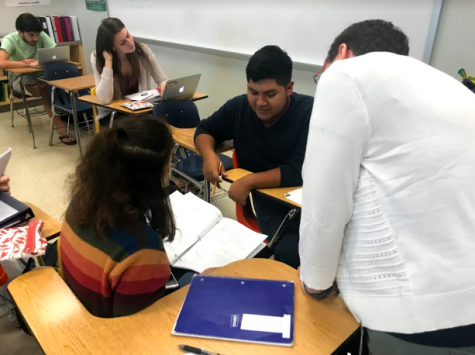 Ms. Scher helps two of her students with their calculus classwork during Generals Period.