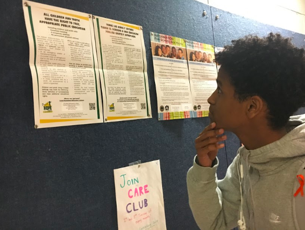Junior Yonatan Belihu looking at public education posters in the main stairway. He is still deciding on whether or not he wants to go to a four-year college or pursue other options.