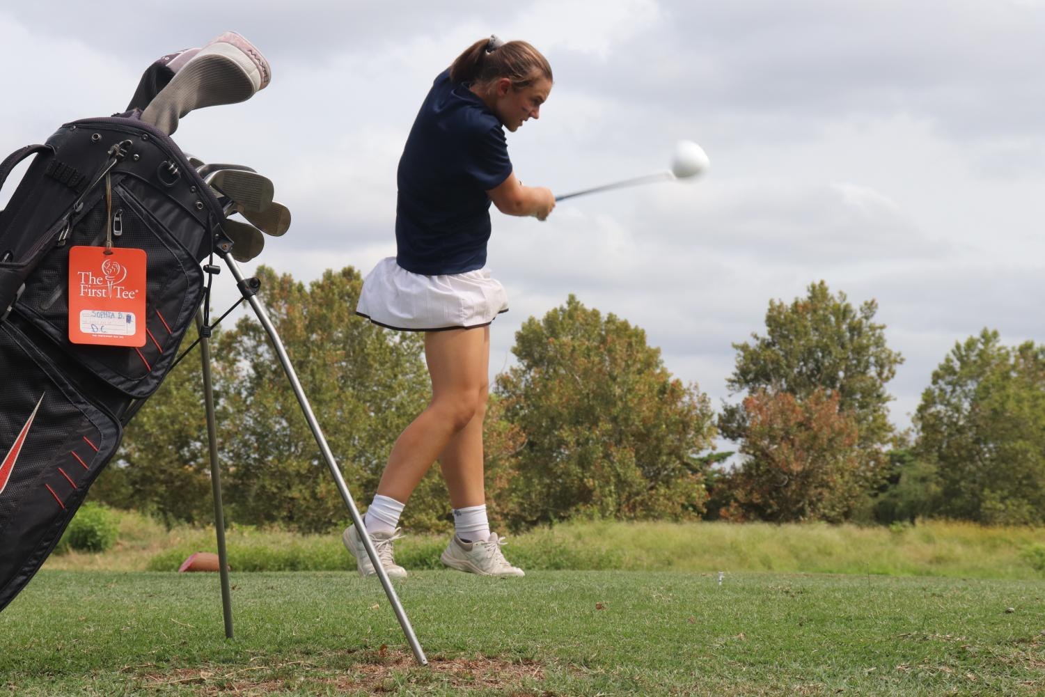 Sophomore Sophia Bandini swings her club during a tournament. The team attends multiple tournaments each season, where they are able to compete against golf teams from other schools.