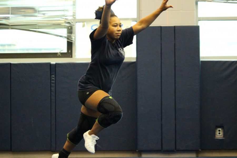 Sophomore Sophia Bailey practices her tumbling skills. Members of the team work hard to maintain these skills in order to perform well at competitions and events such as football games.