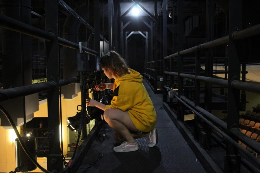 Senior Sarah Shaw works on the lights along the catwalk during a rehearsal. Shaw is the head of the lights department.