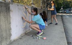 Students decorate the sidewalks near the school with chalk. The SCA's chalk decorating competition was one of their planned Homecoming Spirit Week activities.