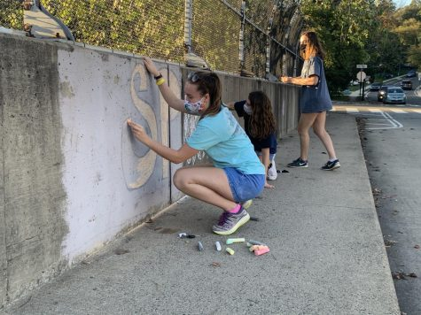Students decorate the sidewalks near the school with chalk. The SCA