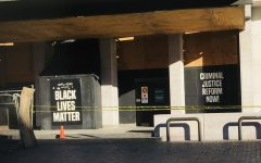A building in Black Lives Matter Plaza has tape covering off an area that was vandalized. The windows of the building are boarded up and there are signs supporting the Black Lives Matter Movement and criminal reform decorating the wall.